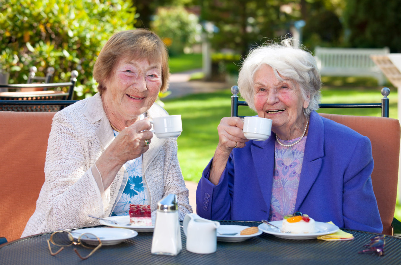 two senior women holding a cup