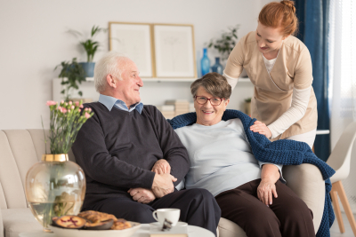 senior couple sitting on a couch with a tender caregiver
