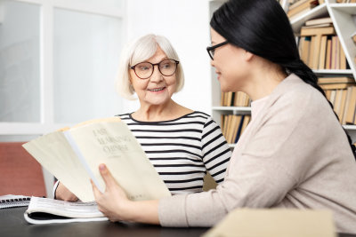 Tutor carrying book while jolly senior woman smiling