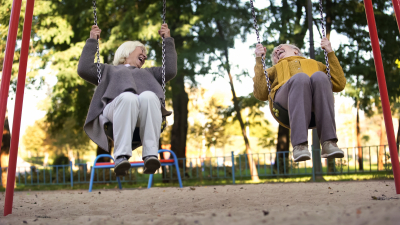 Two elderly women laughing riding swings in park