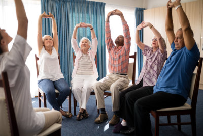 Seniors stretching with female doctor while sitting on chairs at retirement home